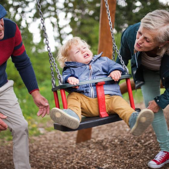 parents and kids on park swings