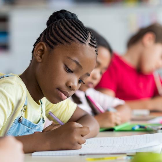 girl writing at school desk